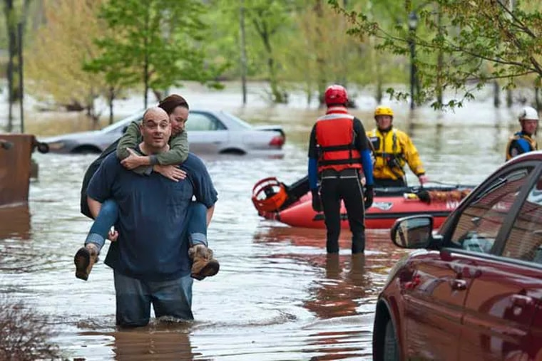 Rene Rivera carries his wife, Melissa Hotsko, from their building at the Riverview Landing Apartments in Eagleville, West Norriton after the Schuylkill River flooded the building's garage and first-floor units. He decided not to wait for rescue boats to arrive. ( RON TARVER / Staff Photographer ) MAY 1 2014