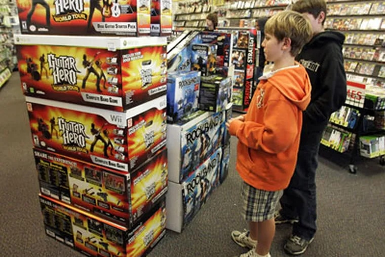 """""""Guitar Hero"""" and """"Rock Band 2"""" video game bundles are seen on display at a GameStop store. As the music industry struggles to cope with falling CD sales, the music video games are helping revive interest in music and providing a lift to sales. (AP Photo / Paul Sakuma)"""