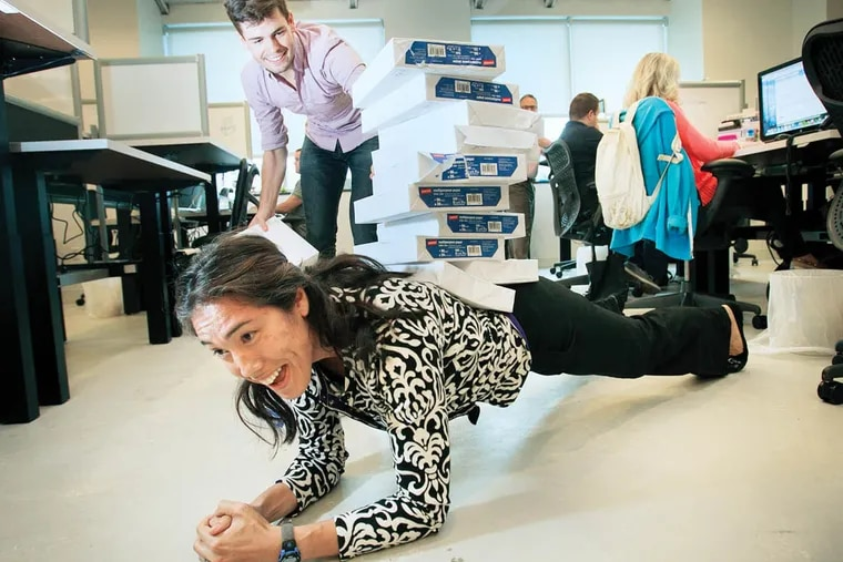 Annitah Patrick, director of consumer products with Leadnomics located at 3020 Market St. in Philadelphia. She is doing the #stackthatpaper campaign to raise funds and supplies for Philadelphia Public Schools. She held the plank position while intern Nick Stropko stacked copier paper on her back. (ALEJANDRO A. ALVAREZ / STAFF PHOTOGRAPHER )