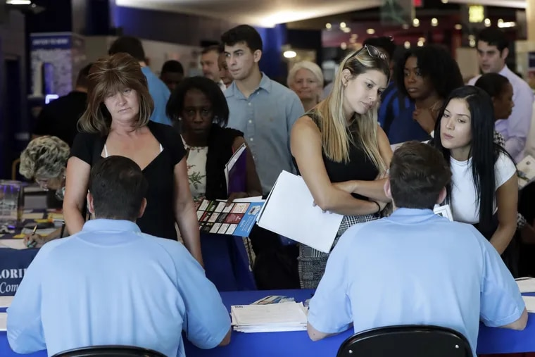 Job applicants talks with representatives from Aldi at a job fair hosted by Job News South Florida, in Sunrise, Fla.