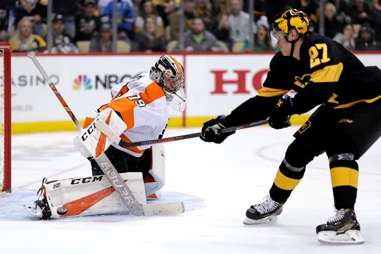 Flyers goaltender Carter Hart (left) stopping a breakaway by Nick Bjugstad late last season in Pittsburgh. Hart made 40 saves in the Flyers' 2-1 overtime win, but he has been inconsistent this season.