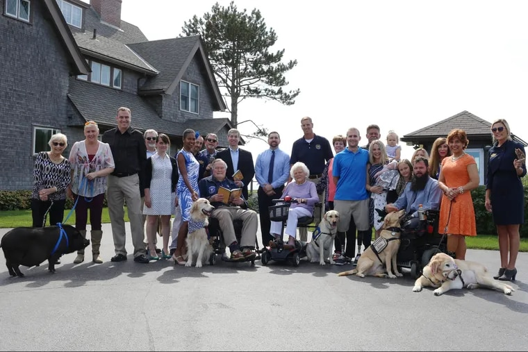 """President George H.W. Bush, First Lady Barbara Bush pose with wounded warriors, their service animals and the authors of the book """"Vets and Pets"""" in Maine in August 2015."""
