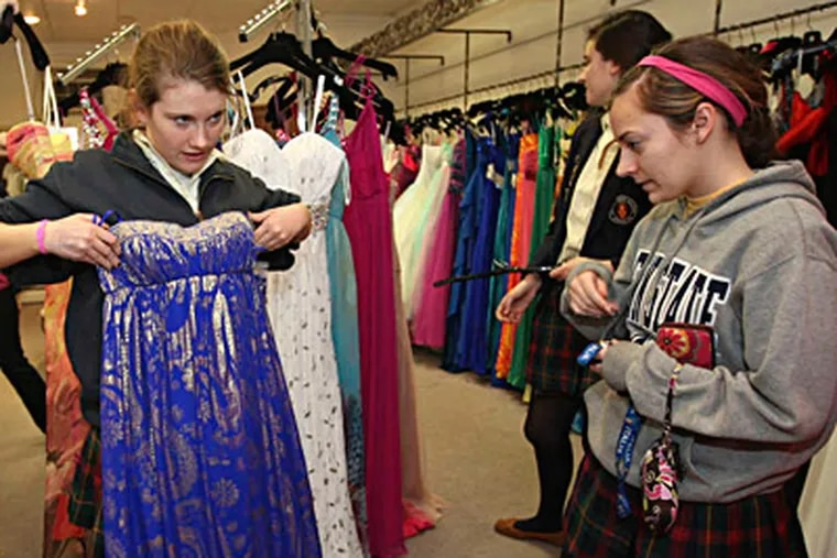 Kate Sullivan, 18, held up a gown last spring to see how it looked in the mirror as friend Lisa Bevilacqua, 18, watched. They both went to Merion Mercy Academy. MICHAEL BRYANT / Staff Photographer