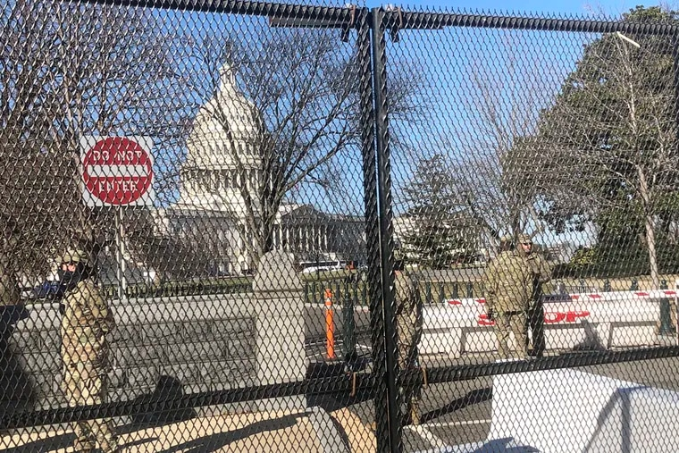 Members of the National Guard stand inside anti-scaling fencing that surrounds the U.S. Capitol, Sunday, Jan. 10, 2021, in Washington, following the attack on Jan. 6.