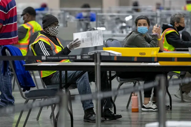 Workers prepare Philadelphia mail ballots to be counted after the November 2020 election at the Pennsylvania Convention Center. The law that greatly expanded mail voting is facing perhaps its most serious court challenges yet.