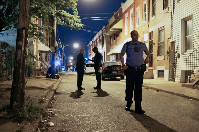 Investigators process the crime scene on the 2200 block of Chadwick Street in North Philadelphia earlier this month. A woman was fatally shot and a man wounded. There have been 203 homicides in 2016.