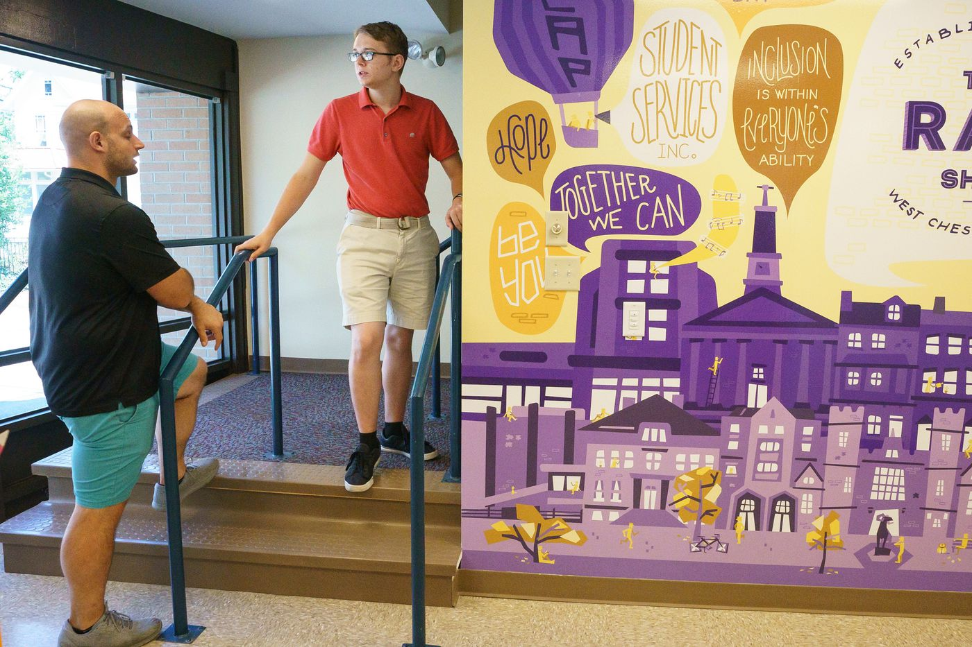 Store manager Bill Marinelli, left, and Tyler Haney, a senior and student worker with autism, at the new convenience store. The mural to the right was painted by students in assistant professor Scotty Reifsnyder's Art 400 Design for Social Good class.