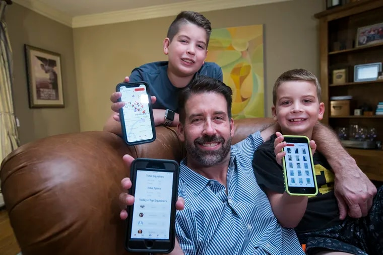 Brad Line's two sons, Greyson, 13, top, and Nolan, 7, pushed him to create an app that would make a game out of killing the spotted lanternfly, an invasive insect that has threatened to cripple Pennsylania's $18 billion grape, tree fruit, and lumber industries. On Saturday, after a month-and-a-half of developing the app, Line, 47, released it to Apple's App Store. It went live Saturday morning and has already attracted a few hundred users, some of whom have already killed dozens of the bugs. They hold up their phones with the app.