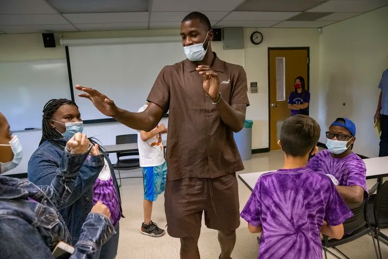 Michael Kidd-Gilchrist high-fives campers during the Speak Now camp at Temple's Ambler campus where he spoke with parents, staff and campers about living with a stutter.