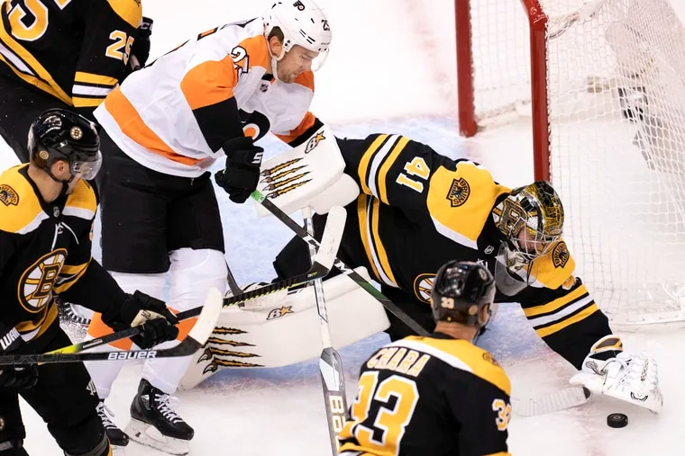 Boston Bruins goaltender Jaroslav Halak (41) covers the puck under pressure from Flyers left winger James van Riemsdyk (25) during the round-robin tourney on Aug. 2. The Flyers and Bruins are among the strong division contenders this season.