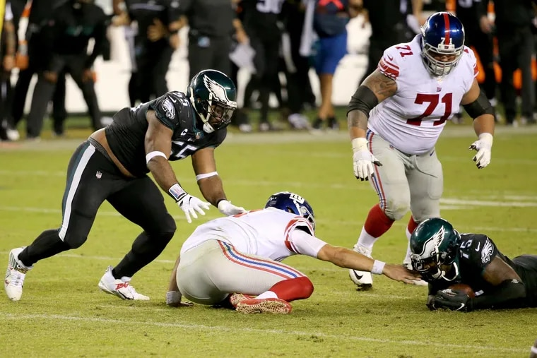 Vinny Curry recovers a fumble by Giants QB Daniel Jones after Brandon Graham (left) knocked it loose.