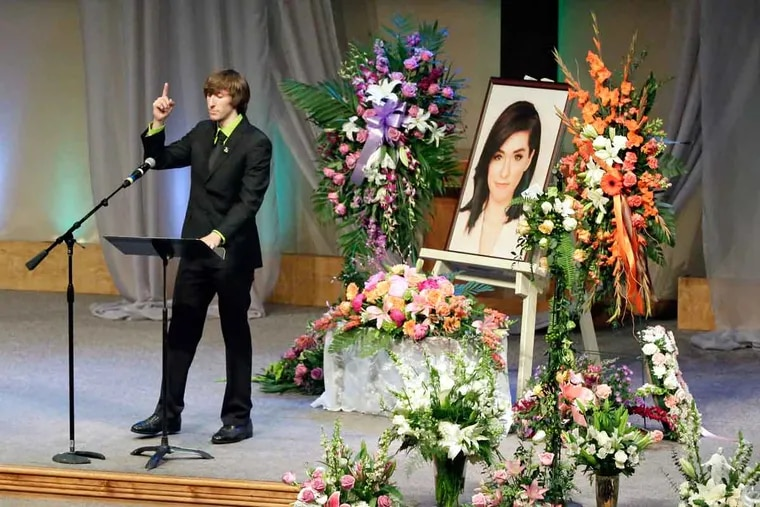 Marcus Grimmie gestures to a picture of his sister. Christina Grimmie was shot to death while signing autographs after a concert.