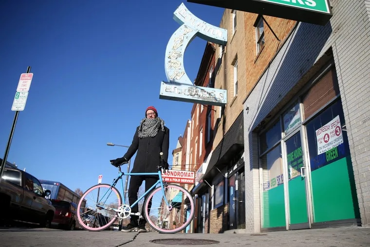 Josa Lazas stands for a portrait with his bicycle outside the Dolphin Tavern along Broad Street on Wednesday, Dec. 13, 2017.