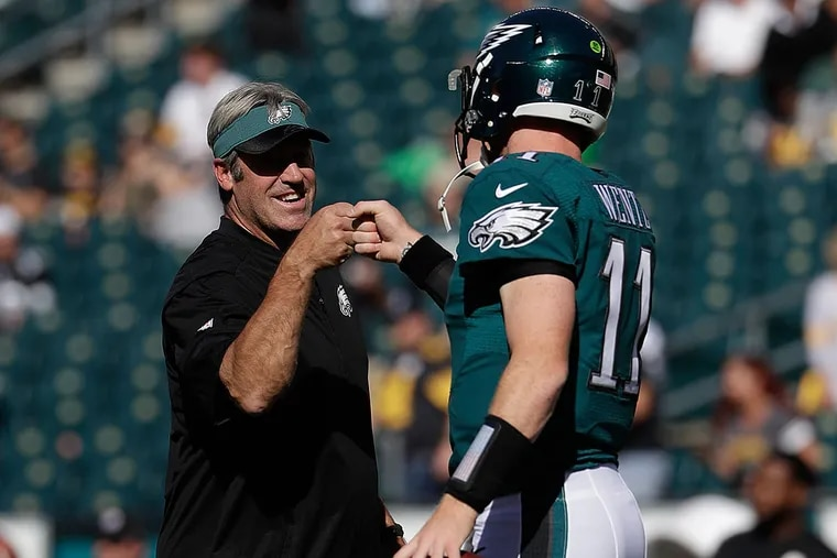 Philadelphia Eagles' Carson Wentz fist bumps head coach Doug Pederson during warm-ups before the first half of a game against the Pittsburgh Steelers on Sunday, Sept. 25, 2016, in Philadelphia.
