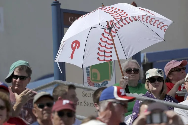 A fan covers herself with a umbrella as the Phillies play the Blue Jays in a spring training game in March in Clearwater.