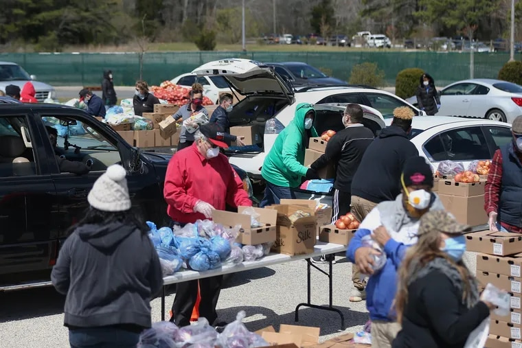 Casino workers and food bank volunteers distribute food for casino workers at Harbor Square in Egg Harbor Township, N.J., on Wednesday, April 22, 2020. Hundreds of cars lined up to receive food at the event, which was organized by Unite Here Local 54 and the Community Food Bank of New Jersey.
