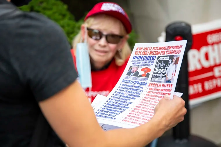 Peggy Boudin, 76, of Ivyland, Pa., a Republican supporting Andy Meehan, hands Angela Delia, 40, of Warwick, Pa., a paper comparing Meehan and Brian Fitzpatrick, at St. Cyril of Jerusalem, on June 2, 2020.