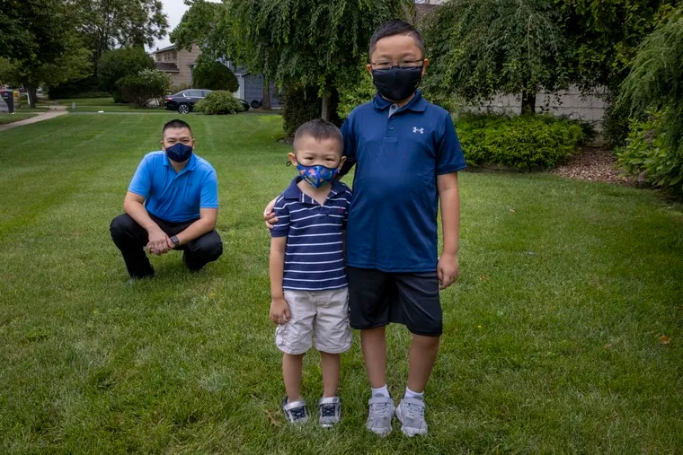 Minh-Tu Do, and his sons Justin, 9, (right) and Joey, 4, who are in the Pfizer vaccine trial, stand outside their home in East Brunswick, N.J.