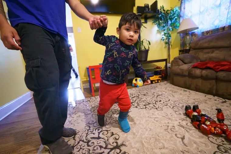Fabian Flores Alameda, age 2, holds the hand of his father, Fabian Flores Aguirre, as he marches across the floor of his family's home in Horsham, Pa. The child is fighting cancer, but the Trump administration has denied the family's request to stay in the U.S. while he gets treatment in Philadelphia.