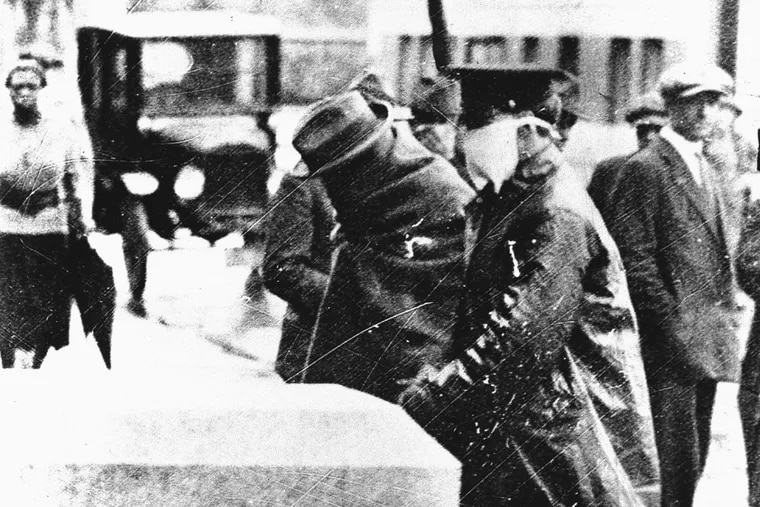An influenza victim, wrapped in a blanket, being escorted by a policeman, who wears a protective facemask of some sort, during the influenza epidemic in 1918.