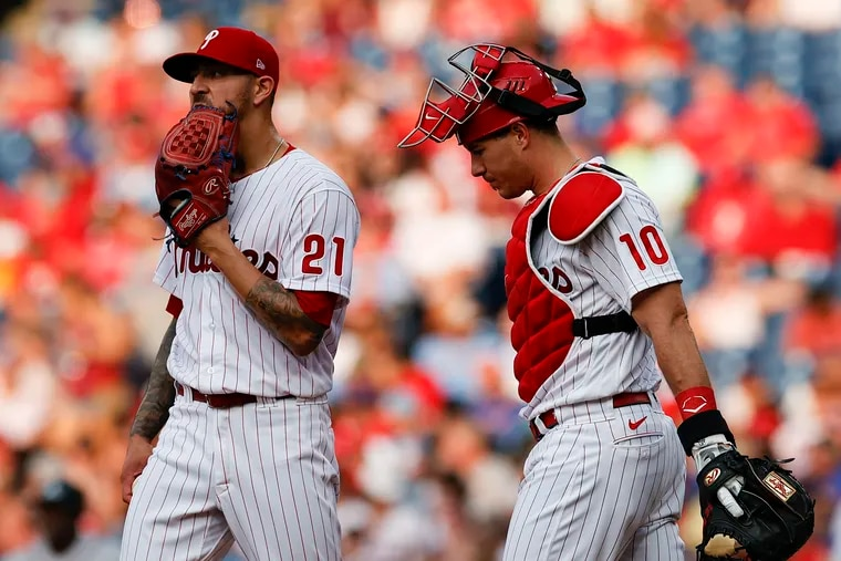 Phillies pitcher Vince Velasquez wipes his face with his glove with catcher J.T. Realmuto in the third inning against the Atlanta Braves on Saturday, July 24, 2021 in Philadelphia.  Velasquez got replaced during the third inning.