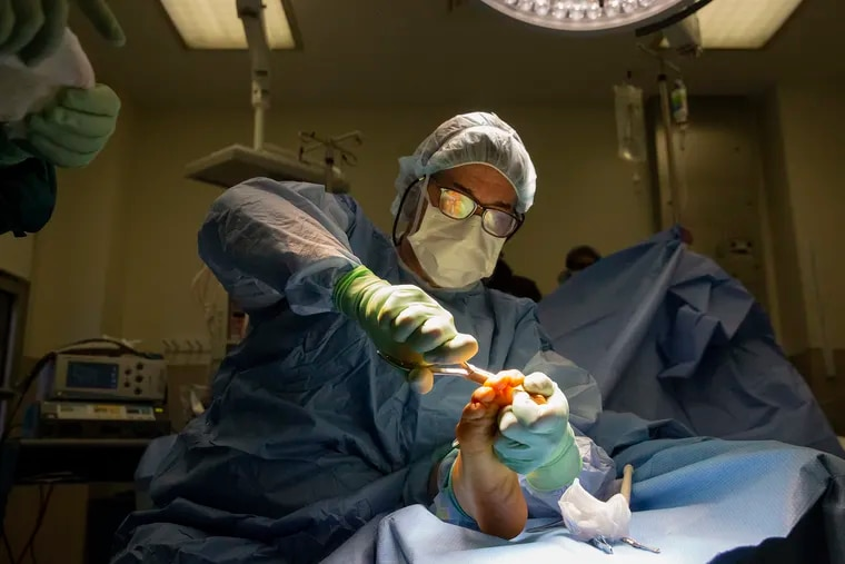 At Pennsylvania Hospital, surgeon Keith Wapner trims the bone in Pattie Bostick-Winn's arthritic big toe before inserting a synthetic implant, called Cartiva, to cushion the joint.
