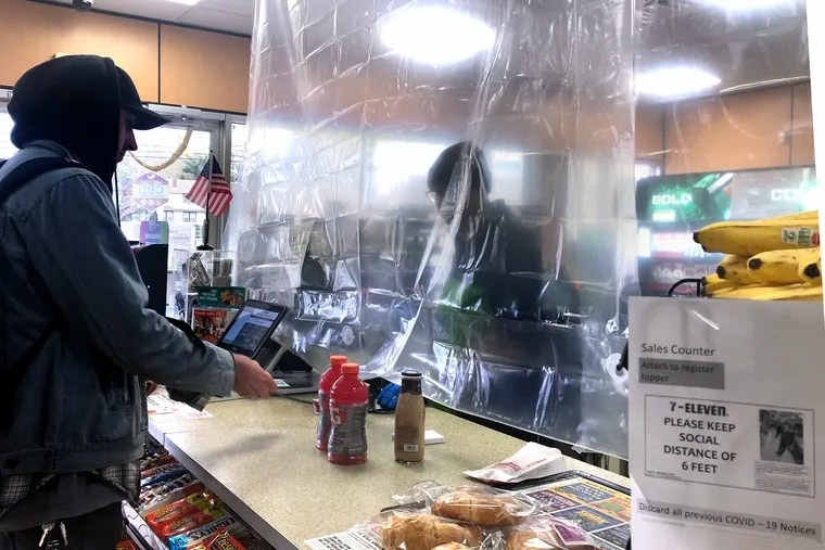 Workers behind the counter at the 7-Eleven on the White Horse Pike in Oaklyn are protected from customers and social distancing by a clear shower curtain March 31, 2020, as New Jersey's shutdown of schools and nonessential businesses because of the coronavirus pandemic continues.