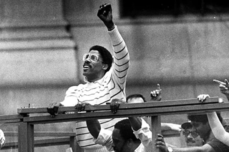 Julius Erving raises his fist to the crowd as he passes City Hall during the Sixers' NBA Championship Parade on Broad Street on June 2, 1983. (April Saul / Inquirer file)