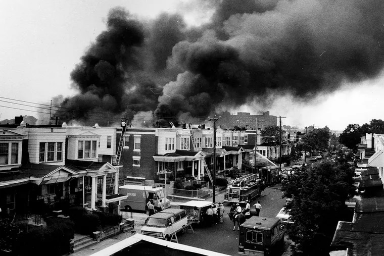 In this file photo, clouds of smoke pour from burning homes after a bombing at the fortified MOVE house on Osage Avenue on May 13, 1985. The resulting fire left 11 people dead, including five children, and burned 61 homes.
