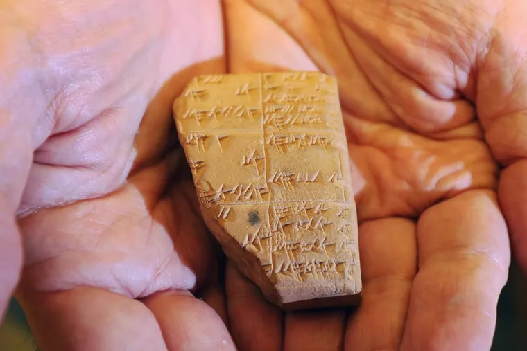 Philip Jones, an expert in cuneiform writings, displays a tablet fragment with the prediction of a solar eclipse on Oct. 23, 425 B.C., at the University of Pennsylvania's Museum of Archaeology and Anthropology. (DAVID SWANSON / Staff Photographer)
