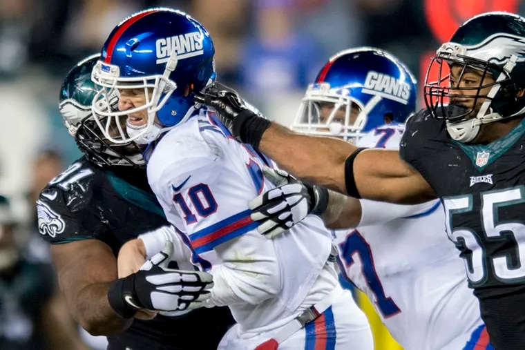 Giants quarterback Eli Manning is pressured by Eagles defensive end Brandon Graham (right) and defensive tackle Fletcher Cox during a 2016 game.