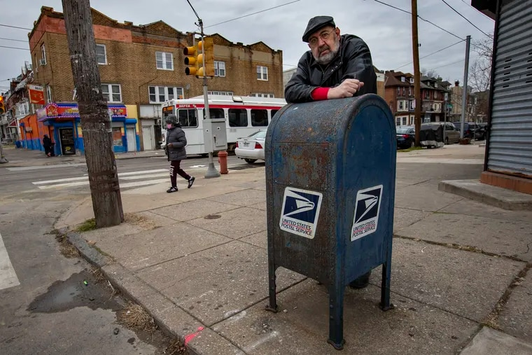 Ian Abrams of Philadelphia at a blue collection box at 51st Street and Chester Avenue. Abrams' check was stolen from the box, then duplicated and forged for $15,000.