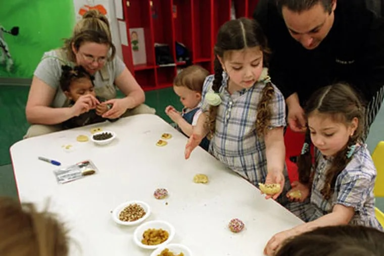 Chef Derek Davis watches children put toppings on their cookies during a cooking class for kids at Colors day-care center in South Philadelphia. (G.W. Miller III / Daily News)